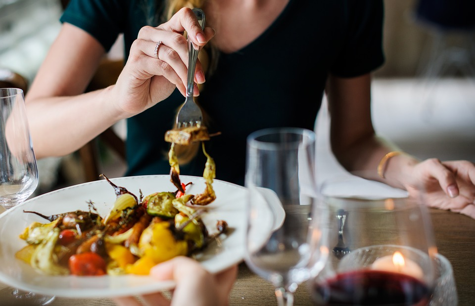 Femme qui mange et pique dans son assiette avec une fourchette