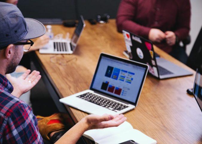 Employés d'une société réunis autour d'une table avec des ordinateurs